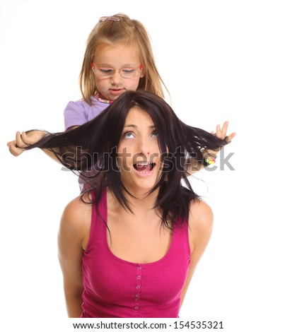 Happy family, cute little girl child playing with mom together doing fun. Daughter and her mother isolated on white