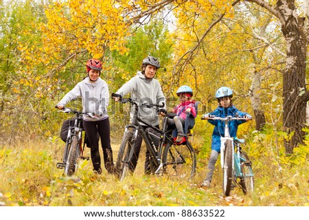 Happy family cycling outdoors, smiling parents with kids on bicycles, golden autumn in park - stock photo