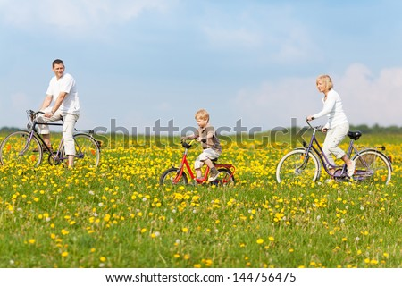 happy family cycling through green fields with flowers - stock photo