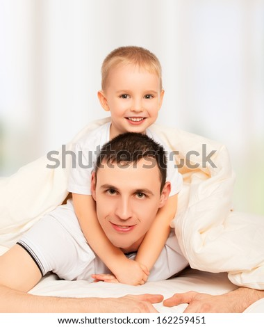 happy family. Dad and son playing and laughing in bed - stock photo