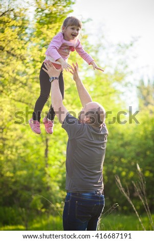 Happy family Dad throws child daughter up on a walk in the autumn leaf fall in park