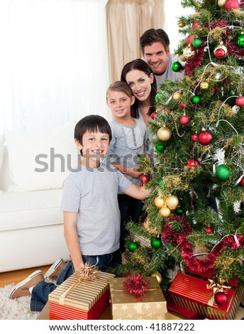 Happy family decorating a Christmas tree with boubles and presents in the living-room - stock photo