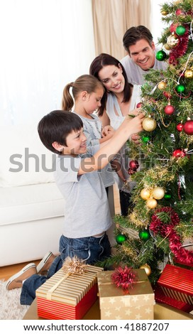 Happy family decorating a Christmas tree with boubles in the living-room - stock photo