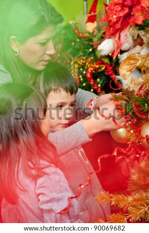 Happy family decorating a Christmas tree with ornaments - stock photo