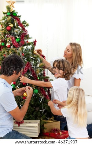 Happy family decorating Christmas tree at home - stock photo
