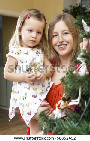 Happy family decorating Christmas tree at home - stock photo