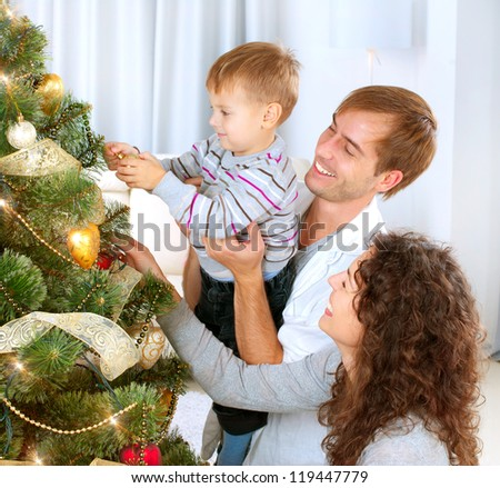 Happy Family Decorating Christmas Tree together. Father, Mother And Son. Cute Child.Kid - stock photo