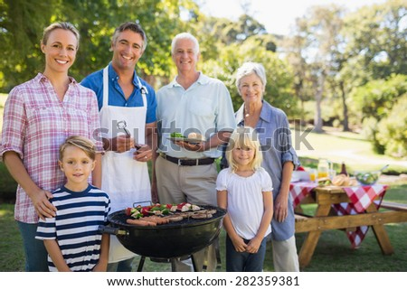 Happy family doing barbecue in the park on a sunny day - stock photo