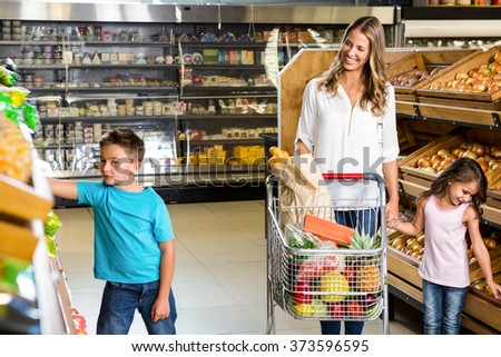 Happy family doing shopping in grocery store - stock photo