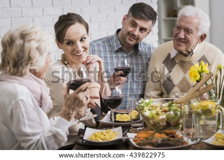 Happy family drinking red wine at the table