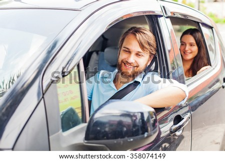 Happy family driving a car - stock photo