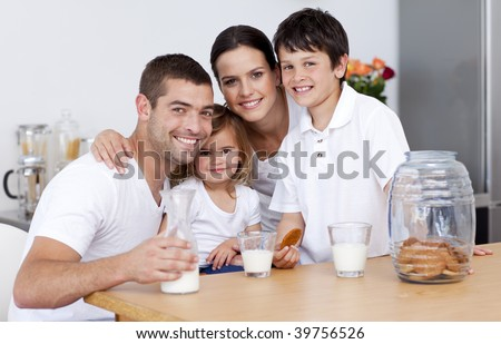 Happy family eating biscuits and drinking milk in the kitchen - stock photo