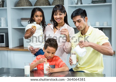 Happy family eating biscuits and drinking milk in the kitchen at home