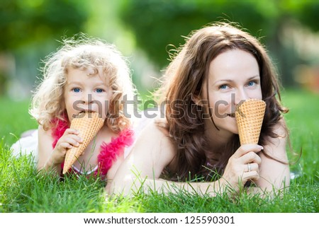 Happy family eating ice-cream outdoors in spring park against blurred green background - stock photo