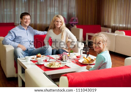 Happy family eating in cafe - stock photo