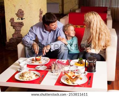 Happy family eating in restaurant. Mother, Father and child in cafe