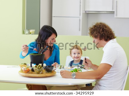 happy family eating meat fondue at home. Copy space - stock photo