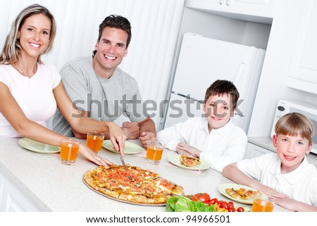 Happy family eating  pizza and vegetables at home.
