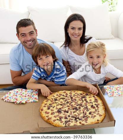 Happy family eating pizza on sofa all together - stock photo