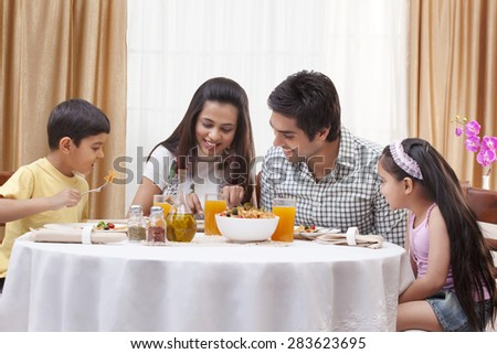 Happy family eating pizza together at restaurant - stock photo