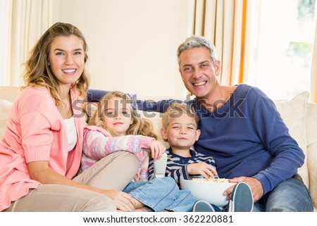 Happy family enjoying a movie together at home - stock photo
