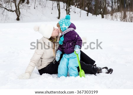 Happy family enjoying beautiful winter day outdoors. The child kisses and loves mom. Winter fun, snow, happy children at winter time. Happy mother and baby playing with snow - stock photo