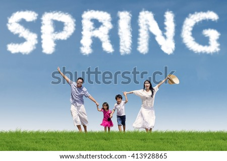 Happy family enjoying leisure time together at the field under a spring cloud - stock photo