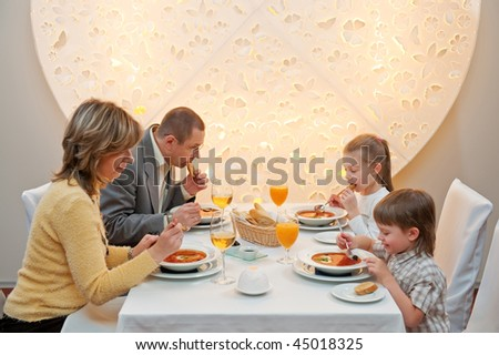 Happy family enjoying meal sitting at restaurant table - stock photo