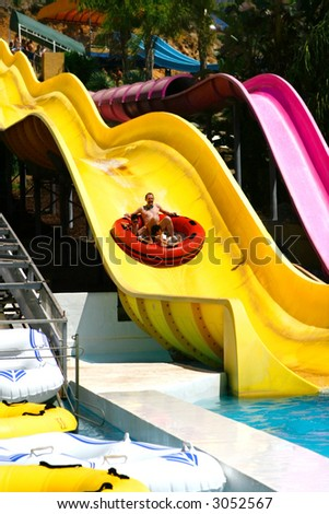 Happy family enjoying the float ride down the big water slide. - stock photo