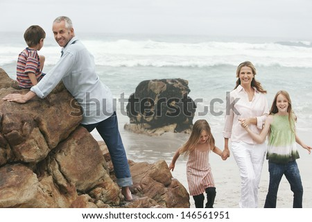 Happy family enjoying their vacation on rocks at beach - stock photo