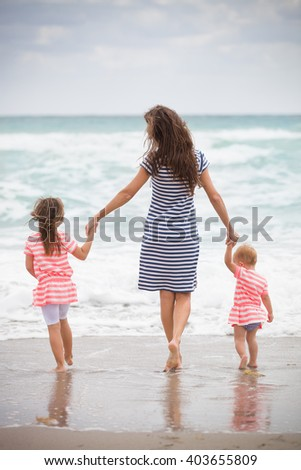Happy family enjoying vacations by the sea. Mother with two little girl walking on the sandy beach. Back view on young woman with two siblings children. outdoors. - stock photo