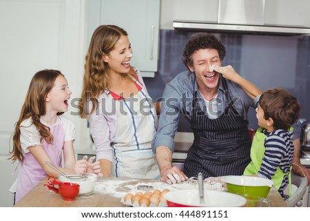 Happy family enjoying while cooking food in kitchen at home - stock photo
