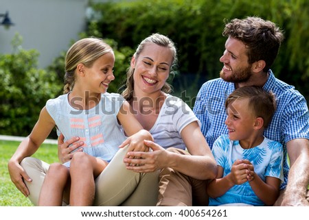 Happy family enjoying while sitting on grass in yard - stock photo
