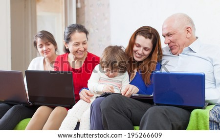 Happy family enjoys on sofa with few laptops at home - stock photo