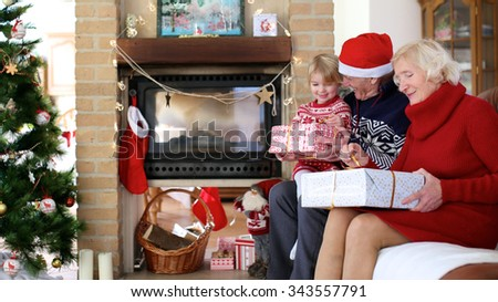 Happy family exchanging christmas gifts in decorated living room with xmas tree and fireplace. Happy loving grandfather giving present to grandchild. Senior woman unwrapping big box. - stock photo