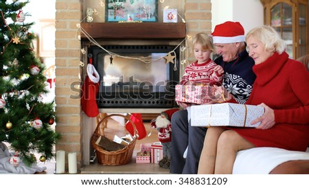 Happy family exchanging christmas gifts in decorated living room with xmas tree and fireplace. Happy loving grandfather giving present to grandchild. Focus on senior woman unwrapping big box. - stock photo