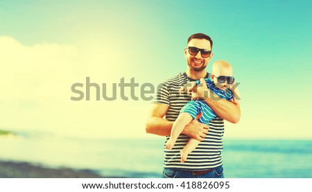 happy family father and baby son on the beach by the sea at sunset - stock photo