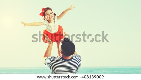 happy family father and child daughter playing and having fun in the summer by the sea on the beach - stock photo