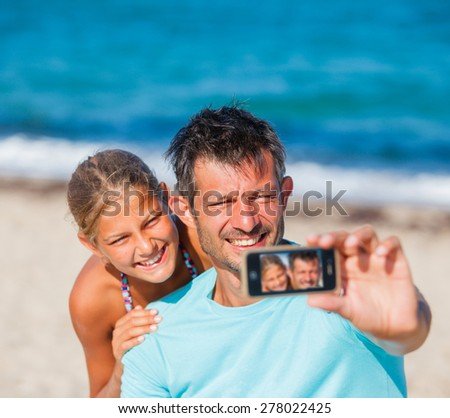 Happy family father and his adorable daughter at beach taking selfie - stock photo