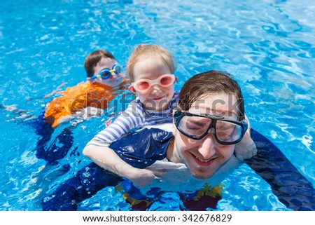 Happy family father and his adorable kids at outdoors swimming pool - stock photo