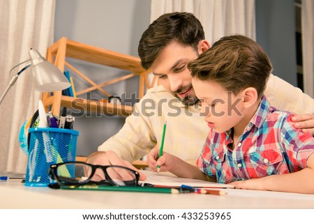 Happy family. Father and son doing homework together - stock photo