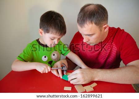 Happy family. Father and son working at home - stock photo
