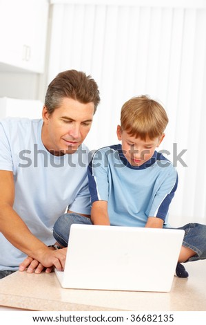 Happy family. Father  and son working with laptop.