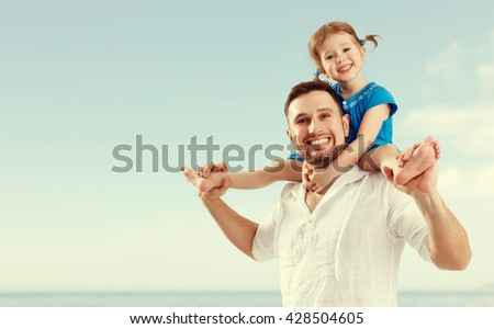 happy family father  day. dad and child daughter playing and having fun in sky