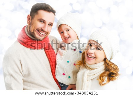 happy family father mother and child daughter on a winter walk outdoors - stock photo