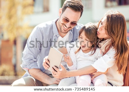Happy family. Father, mother and daughter in the city take selfie and have fun.