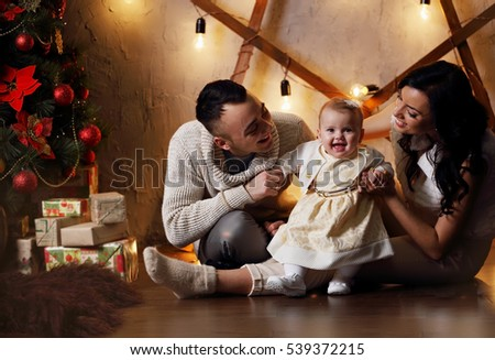 Happy family, father, mother and daughter near the Christmas tree