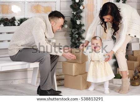 Happy family, father, mother and daughter on the porch with Christmas decorations. first steps