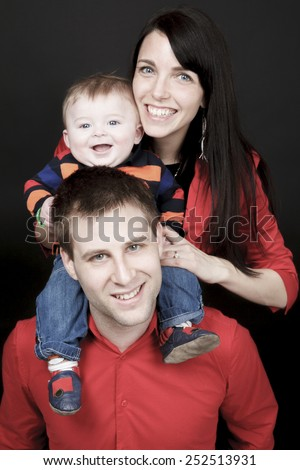 Happy family, father, mother and infant in front of a black background - stock photo