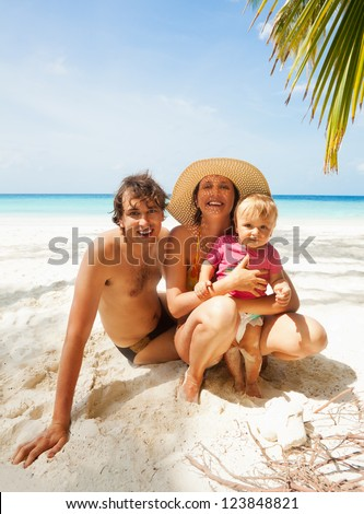 Happy family - father, mother and kid - toddler sitting on the beach - stock photo